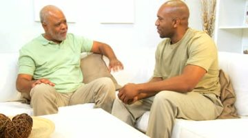 stock-footage-african-american-father-and-son-chat-together-on-a-couch